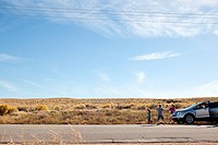 Three children by parked car in desert (thumbnail)