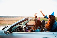 Three young women wearing party hats in convertible car