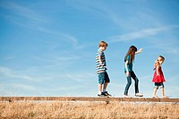 Three children walking along wooden fence