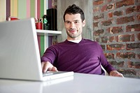Young smiling man sitting in office and using laptop