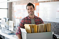 Portrait of smiling man holding box with files in office