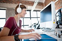 Smiling woman with headphones using computer in office