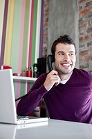 Smiling man on phone in office
