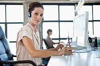 Portrait of young woman with headset in office