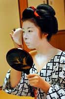 A MAIKO APPRENTICE GEISHA WITH HER TRADITIONAL MAKEUP DORAN. APPLICATION OF RICE POWDER WITH A SPONGE KONYAKU ON HER FACE OVER THE WHITE FOUNDATION SH...