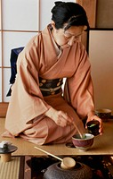 THE JAPANESE WOMAN, MASTER OF CEREMONIES, POURING THE POWDERED GREEN TEA MATCHA INTO A BOWL CHAWAN TO THEN DILUTE IT WITH HOT WATER, THE TRADITIONAL T...