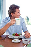 Mature man at breakfast table looking sideways
