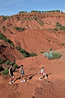 HIKING ON THE RED EARTH HILLS OF THE DJEBEL KLELOUT NEAR THE BERBER VILLAGE OF OUTGHAL, AL HAOUZ, MOROCCO
