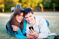 Couple in grass looking at cell phone