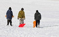 England, Essex, Basildon. Three young boys walking across a snow covered field with their sleds.