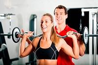 Personal Trainer und Frau im Fitness