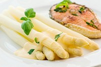 Asparagus with salmon fillet and sauce as closeup on a white plate