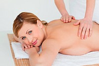 Lovely blond_haired woman getting a massage in a spa centre