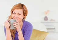 Smiling red_haired woman holding a cup of coffee and posing while sitting on a sofa