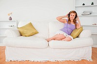 Smiling red_haired woman listening to music and posing whle sitting on a sofa