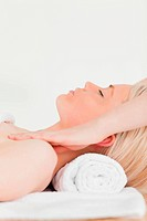 Attractive blonde woman enjoying her treatment while lying down in a Spa centre