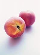 Two peaches on white background