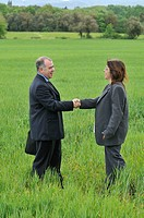 businesswoman and businessman shaking hands in green nature