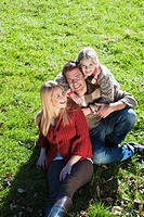 Austria, Flachau, Salzburg, Family sitting on autumn meadow