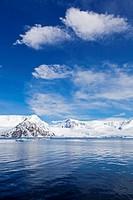 South Atlantic Ocean, Antarctica, Antarctic Peninsula, Gerlache Strait, View of iceberg with snow_covered mountain range