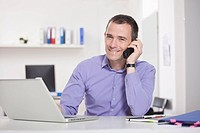 Germany, Bavaria, Munich, Businessman on phone in office
