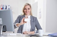 Germany, Bavaria, Munich, Businesswoman showing blank business card in office, smiling, portrait