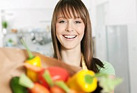 Germany, Cologne, Woman standing in kitchen with vegetables bag