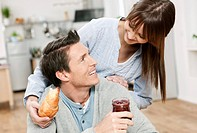Germany, Cologne, Man and woman in kitchen, woman holding croissant