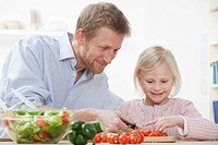 Germany, Bavaria, Munich, Father helping daughter to prepare salad, smiling