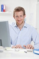 Germany, Bavaria, Munich, Businessman using computer, smiling, portrait