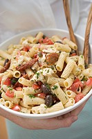 Woman holding a bowl of pasta salad with tomatoes & olives