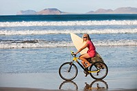 Girl riding mountainbike to the surf