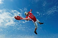 American footballer in mid air stretches to make the catch