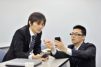 Young businessmen using and showing smartphone