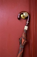 An umbrella hanging on a doorknob