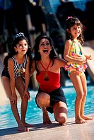 Mother standing beside a swimming pool with her two children