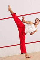 Young man kicking while practicing karate