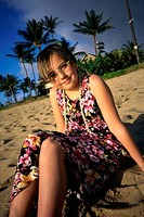 Portrait of a girl sitting on the beach smiling