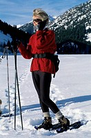 Senior woman standing in the snow talking on a mobile phone
