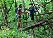 Italy, Piedmont, Father helping son cross rickety bridge holding mountain bike