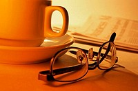 Close_up of eyeglasses near a cup of coffee