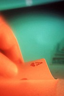 Close_up of a person's hand lifting an ace of hearts