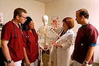 Female doctor using a human skeleton to teach medical students in a medical class