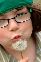 Close_up of a girl blowing Dandelion seeds