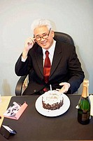Portrait of a businessman celebrating his birthday in an office