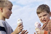 Side profile of two boys holding ice cream cones