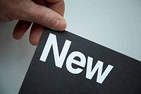 Hand holding card highlighting the word new