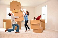 Couple moving into new house, man carrying several boxes