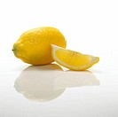 Reflection of a whole and a wedge of lemons on a table