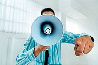 Businessman shouting into a megaphone in an office